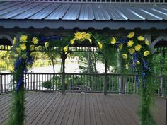 Cypress wedding arbor decorated in yellow and blue flowers