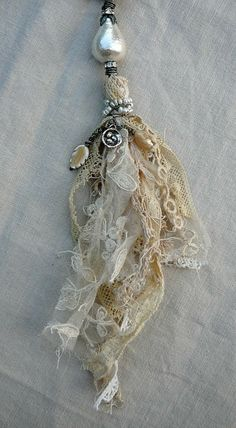 Beautiful tassels made with remnants of muslin,pearls and vintage lace ~by Nina Bagley .I see a beautiful spirit doll represented in this lovely tassel. Textile Jewelry, Fabric Jewelry, Jewellery, Fabric Art, Fabric Crafts, Jewelry Crafts, Handmade Jewelry, Arts And Crafts, Diy Crafts