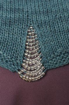 Love the beading of the side slit on this tank top in the 2012 issue of Interweave Knits.
