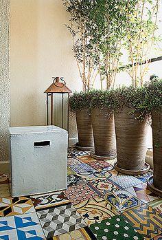 Sem muito espaço para transformar esta varanda de 3 m² com móveis, vasos e plantas, a arquiteta Cláudia Xavier alterou o piso, apostando no ladrilho hidráulico. Os vasos de cerâmica com murtas encobrem a vista pouco atraente e trazem verde para a sala