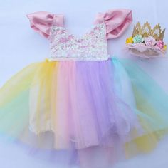 Unicorn Birthday Party? This tutu romper and dress with a pastel full tutu is a must have. Beautiful Pastel Full Tutu with sequin bodice and satin flutter sleeves. The sequin top is a halter. The neck ties help you adjust to the desired length. It is lined to prevent scratching. This listing is for the Sparkle Romper® only. We do not make or sell the accessories. Please visit our FAQ page for current production time and sizing info. These fit true to size. Care: Hand wash in cold water...
