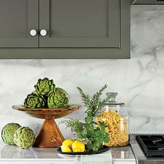 """Bathing the kitchen in color creates a cozy, friendly feel. """"The one thing I had to have was white knobs,"""" says Phoebe. """"I love how they pop against the dark green."""""""