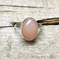 A lovely elegant peach pink oval moonstone has been set in sterling silver with a handmade sterling silver ring band. This stone is romantic and has a 'cat eye' luminescent quality to it. The color ranges from peach to a light pink depending on the light. It is 10mm x 14mm in size.   Size 5.5.