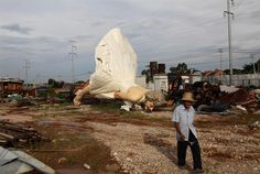 Man walks past giant statue of U.S. actress Marilyn Monroe, dumped at a garbage collecting company in Guigang, China. Giant statue was dumped at a garbage collecting company this week for unknown reasons.