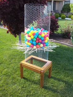 """Backyard Ker-Plunk"". I made this DIY Ker-Plunk game by upcycling an old end table I found on craigslist. We wrapped some chicken wire around the top, stapled it in place to secure, and voila! Homemade Ker-plunk! We got the wooden dowels at Home Depot and I found the ball pit balls on craigslist. But of course, you can get them at Walmart or Toys R Us. It's a ton of fun!"