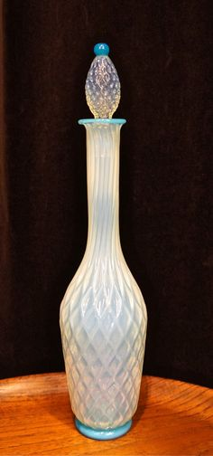 A  display of glass techniques we don't ever see combined in one piece. Attributable to Fratelli Toso, this stoppered bottle of opalescent glass has been cage-blown for a quilted effect. Impressive in its complexity. The tone is a dreamy mother-of-pearl with a hint of my favorite accent color - turquoise.  14""