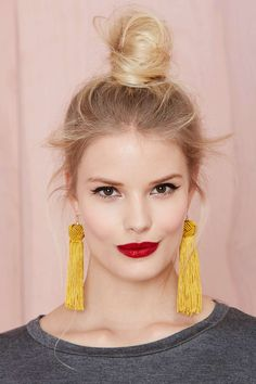 Yes to topknots, festive red lips, and statement earrings