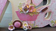 Nome  Lívia em MDF decorado com a  técnica de scrapdecor, letras  foradas com  papéis de scrapboook, flores feitas  a partir de  furadores. Menina  com  flores comprada  no site da silhuette Design. Carrinho de mão  com  flores.
