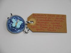 Pillsbury?s Pieces No, 161.  Pin - metallic paleblue capsule with pale blue paper butterfly.  In exchange for a donation to KATHMANDU ANIMAL TREATMENT CENTRE, Nepal.  Available at St. George's Church, Madrid on Saturday 13 June from 11.00 - 15.00.