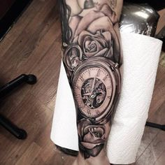 Timepiece arm tattoo with roses.