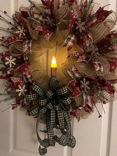 This primitive Christmas Wreath is adorned with rustic rusty metal snowflakes and red pip berries, berries and greenery. A large flickering candle accents the center. The wreath is made of ivory poly burlap mesh and accented with reddish burgundy snowflake ribbon and checked ribbon als #Snowflakes