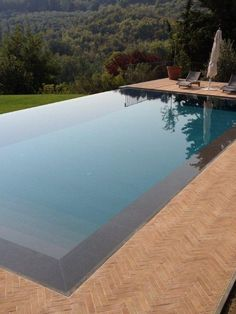 Infinity swimming pool Infinity swimming pool with waterfall by INDALO PISCINE