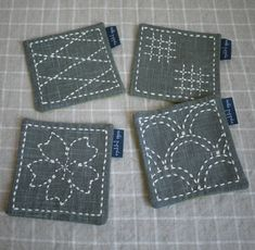 """Sashiko coasters by Saké Puppets Sashiko 刺し子 is a Japanese style of needlework. Literally meaning """"little stabs,"""" Sashiko was originally used to strengthen and reinforce fabric through a series of running stitches."""