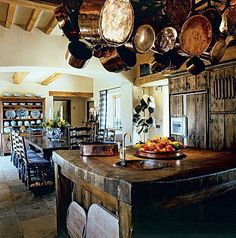 This Tudor-style space is full of charm. The hanging copper pots and pans, antique china dishes, and distressed dark wood would fit right into a historic castle.