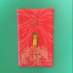 DIY: Switch plate in the nursery covered in Lilly Pulitzer tissue paper and 'taboo' print elephant cut out. So simple and another pop of pink :)