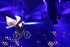 Is it a bird, is it a plane? A stuntman equipped with a pair of wings soars on a bicycle above spectators at the Opening Ceremony