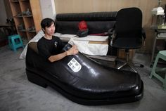 (HA HA! AWESOME.) Chen Mingzhi, a shoe designer, sits inside of his handmade 1.9 metre-long (6.23 foot-long) right shoe at his family store in Wenling, Zhejiang province September 27, 2012. Chen, new to the business of shoe-making, was challenged by a neighbour to create a big shoe. The leather right shoe weighs 38 kg (83.8 pounds) and took him two months to make at a cost of 2,000 rmb ($317.30). REUTERS/Carlos Barria