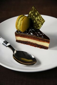Chocolate and matcha entremet with chewy dark chocolate brownie layer, vanilla crémeux, chocolate joconde cake, a thin layer of matcha mousse, chocolate mirror glaze, and a matcha macaron.