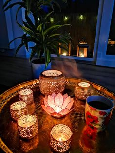 Brass tea tray from Morocco, golden damask tealights and a lotus candle holder from India.