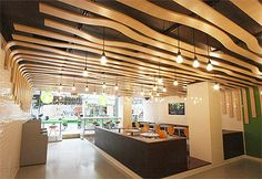 Organically Shaped Wood Planks On The Ceiling Are Hanging Down Walls Resembling Fettuccine