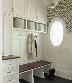Chic mudroom features a row of cabinets suspended over a row of cubbies filled with three flannel bins and a wood mudroom bench with wainscoting trim above.