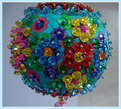 Pingente natalino confeccionado com bola de isopor revestida em tecido e adornada com lantejoulas, pedrarias, cristais, miçangas.