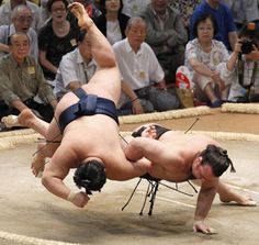 Sumo wrestlers defying gravity!     Kotooshu loses the match with his hand touching the ground while Goeido stays aloft another split second.