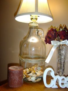 Transform a glass jug into a beautiful lamp base. Fill it with shells or misc. items of sentimental value to add warmth & light to your home!