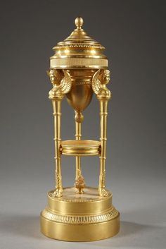 A pair of tripod perfume burner in gilded and chiselled bronze composed of a double circular base and three pilasters decorated with rings and terminated with claw feet. They support...