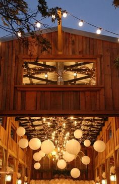 A barn lit with a canopy of lights and paper lanterns