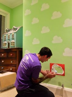 Sam stencilling the cloud wall.
