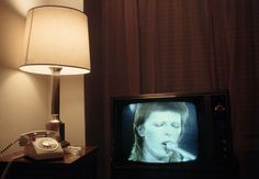 David Bowie performs as Ziggy Stardust on TV in a room at the Delmonico Hotel. | by Henry Diltz, New York, c1974