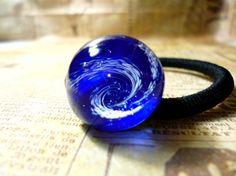 紺色のガラスの中に渦模様が入ったガラスのヘアゴムです。立体的な渦の底に銀箔が輝くどの角度から見ても楽しめるデザインです。ガラス:直径約2cm 高さ約1.4cm...|ハンドメイド、手作り、手仕事品の通販・販売・購入ならCreema。