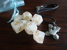 This matched set of polyhedral dice for playing Dungeons and Dragons, Pathfinder, or similar roleplaying games consists of a full set ( d 20, 2d10 / percentile, d12, d8, d6, d4). A clear blue mesh bag makes it easy to find the die you need - no fumbling! The dice are ice white with gold numbers.  A Diddl mouse charm necklace, V for Victory, is included for an extra bit of luck!