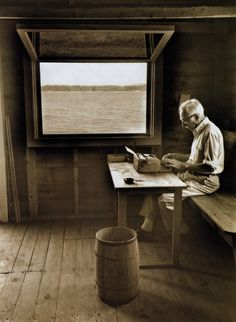 E.B. White writing in his boathouse