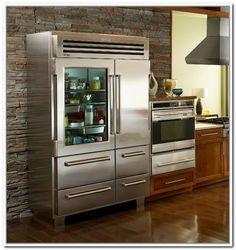 Sub zero pro 48 with glass doors someday when i have 1450000 to with wooden cabinetry and glass window and smoke stack and microwave and glass front refrigerator residential stacked on stone wall sub zero glass door planetlyrics Images