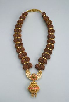 India | Garland of berries. Double rudraksha seeds from the utrasam tree (Eleocarpus ganitrus), sacred to the Hindu god Shiva, alternating with gold spacer beads. Pendant, Gold, silver, diamonds and rubies. | ca. late 19th to early 20th century