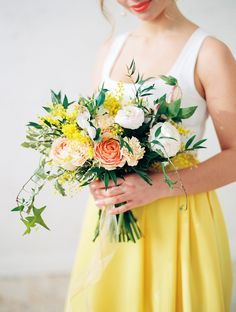 Pretty Hand Tied Wedding Bouquet Featuring: Peach Garden Roses, Pastel Peach Carnations, White Ranunculus, Yellow Mimosa Flowers, Greenery + Foliage
