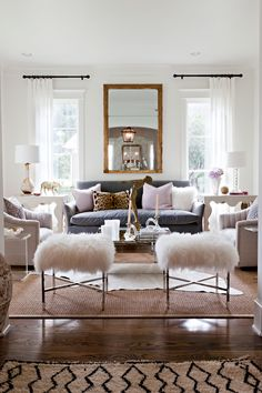 White living room with blue and gold accents. Very pretty. Don't you love those fuzzy white stools?