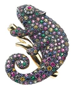 Unique brooch in yellow gold and silver carved a natural chameleon on a branch, entirely set with multicolored sapphires and emeralds, eye adorned with a ruby cabochon finely emphasized brilliant-cut diamonds. Accompanied by a small fly in gold, set with onyx, an emerald and brilliant-cut. Diamond. Signed Friedrich.