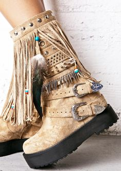 Current Mood Sedona Wedge Boots ...we wanna watch the sunset in tha southwest with ya, babe. These dope boots feature an ultra soft tan vegan suede construction, thick platform sole, tons of drippy fringing wit feathers 'N beads hangin' around the leg opening, rows and rows of spikes, studs, 'N grommets, concealed wedge to give ya sum height, two buckles wit etched hardware wrapped around tha ankle, and side zip closure.