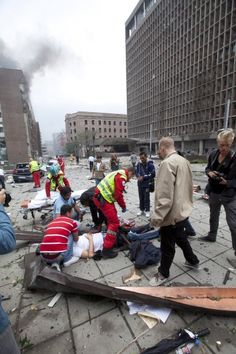 Rescue officials tend to a wounded man after a powerful explosion rocked central Oslo