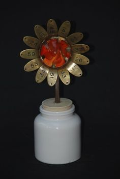 flower, glass, mixed media, reclaimed, recycled, sculpture An old found glass paperweight, a small copper saucepan, a brass cloakroom tags and a used mustard jar and you have a flower !  ++ More information at Sophie Marsham website ! Idea sent by Sophie Marsham !