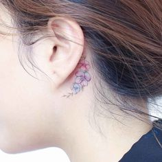 small flowers tattoo behind the ear