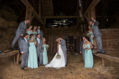 The bridal party looks at the bride and groom kissing as they stand in the middle of the barn, dressed in rain soaked tuxedos completely drenched