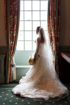Stunning dress as bride gazes out of the window | Chilston Park Hotel