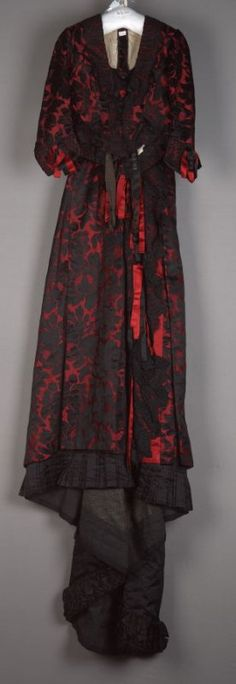 Woman's dress: bodice and skirt Date: ca. 1880 Media: Red And Black Brocade, Satin, And Lace Country: United States Accession Number: 78.72.2a-b Button front bodice with low square neckline and 3/4 length sleeves.Trimmed at neck, Cf, waist and cuffs with black lace. Trimmed at cuffs and CB with loops of red and black ribbon. Brocade skirt has red/black shot silk bustle , black lace and ribbons trim left front.