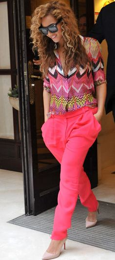 Beyonce looks too cool in a multi-colored Carven shirt and popping pink, pleaded-front pants by Vionnet