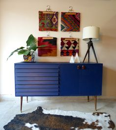 Navy blue credenza with wooden legs and faceted gold accented knobs. Styled with kilim pillow covers and a cowhide rug