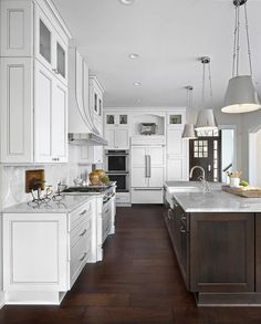 Large White Kitchen Boasts An Exquisite Dark Brown Island Topped With Marble Countertops Holding A Farmhouse Sink Ed Polished Nickel